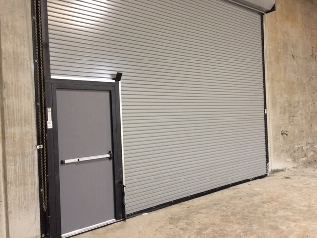 greenville door company overhead door with a passenger door inside it.