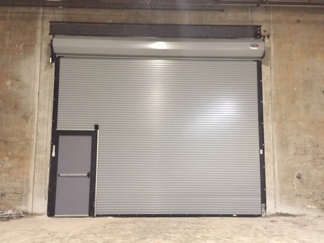 anderson sc door company overhead door with a passenger door inside it.